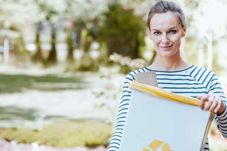 Bewuste activist die om het milieu geeft door afval in een grijze bak te recyclen