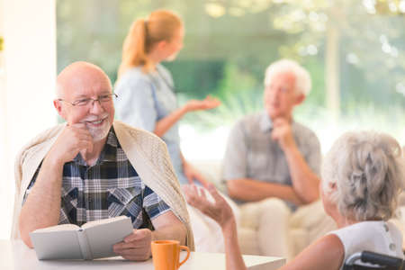 Senior man enjoying time while sitting at a table and talking about hobbies with a friend
