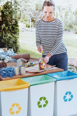 Dona de casa colocando rolhas coloridas de garrafas em frasco de vidro ao classificar os resíduos no terraço