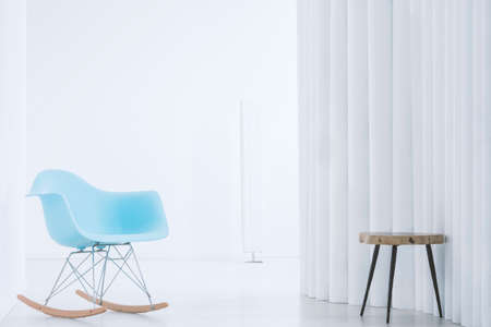Blue rocking chair and wooden stool in bright interior with creative wall Banco de Imagens