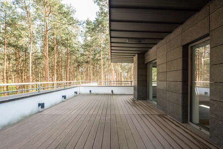 Large shaded  balcony with the view on forest with wooden floor