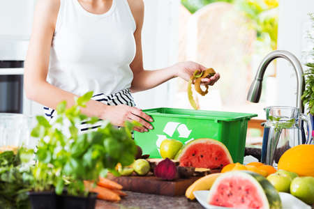 Close-up of eco friendly woman disposing of leftovers into compost bin while preparing salad