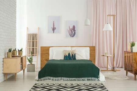 Donkere deken op kingsize bed en geometrisch tapijt in rustieke slaapkamer met houten meubilair