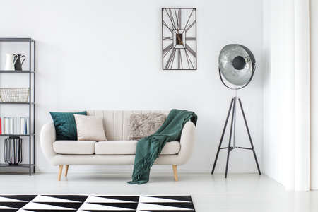Green blanket on beige settee in bright living room with lamp and clock on white wall with copy space