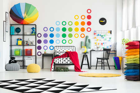 Black and white carpet and yellow rug in bright bedroom with colorful dots and rainbow umbrella