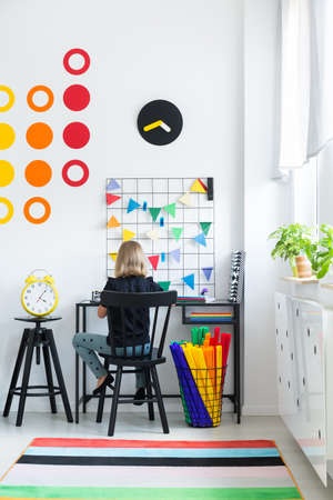 Little girl sitting by a desk doing homework in white room with colorful carpet 版權商用圖片