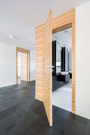 View of neat corridor with open wooden doors to the bathroom and room Stok Fotoğraf