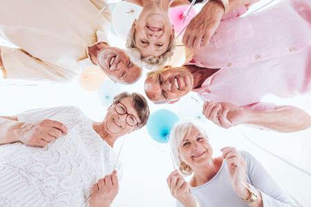 円の中に立っている高齢者の友人のローアングルは、会議中に一緒に楽しい時を過す