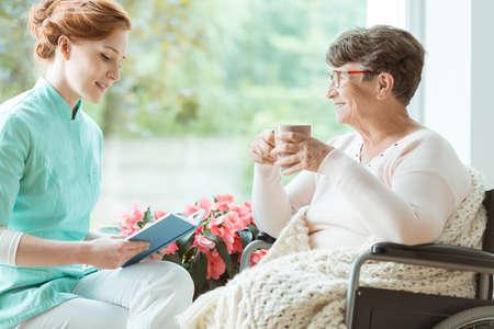 길잡이 휠체어를 병원 방에있는 노인에게 책을 읽는 파란색 제복을 입은 보조자 스톡 콘텐츠
