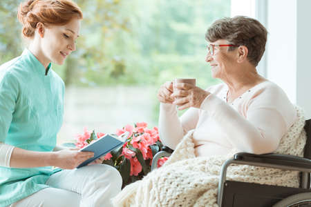 Assistant in blue uniform reading a book to elder woman in wheelchair in a hospital room Stock Photo - 91657659