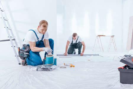 Renovatiebemanning tijdens interieurafwerking in het nieuwe kantoor om de muren te schilderen