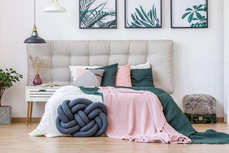 Knotenkissen und grüne und rosa Bettwäsche auf Bett im gemütlichen Schlafzimmerinnenraum mit Lampen, Plakaten und Koffer Standard-Bild - 91680455