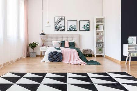 검은 색과 흰색의 카펫과 식물, 분홍색과 초록색의 침대 시트가있는 넓은 침실 인테리어, 베이지 침대 겸용 침대 스톡 콘텐츠