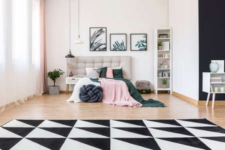 Black and white carpet and plant in spacious bedroom interior with pink and green bedsheets on bed with beige bedhead