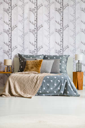 King-size bed with brown and grey pillows between lamps on wooden stools against forest wallpaper in bright bedroom