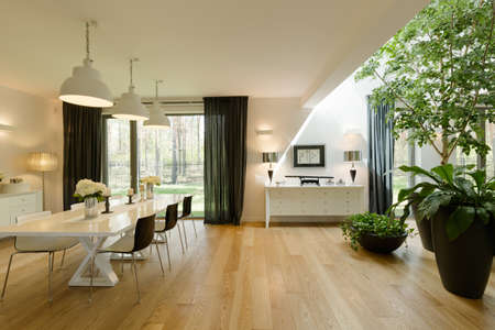 Open and spacious living room with a large window and a dining table Imagens