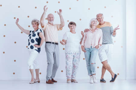 Group of senior people dancing together during a birthday party in bright room with gold dots wallpaper Stockfoto