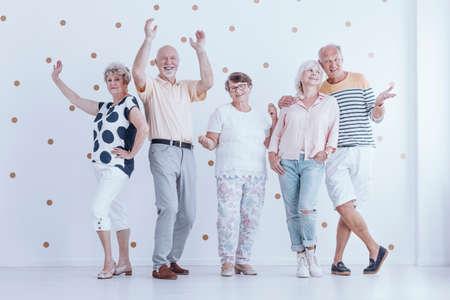 Grupo de pessoas sênior dançando juntos durante uma festa de aniversário na luminosa sala com papel de parede de ouro pontos Foto de archivo