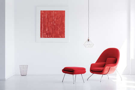 Lamp above red armchair and stool in white interior with basket and red painting on wall Foto de archivo