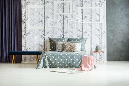 バスケットの敷物とピンクの毛布で広々 とした灰色の毛皮枕キングサイズのベッドの横にある青いベンチ