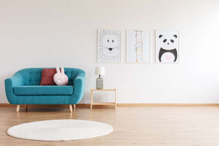 Lamp on wooden stool and round white rug in kids room with turquoise sofa with pink pillow and posters on the wall