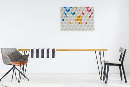 Copy space on a wall with poster in simple dining room with chairs at a long wooden table with striped cloth