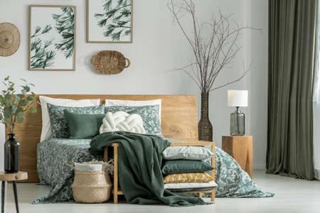 Pillows and blanket on cabinet in khaki bedroom with wooden furniture and white pillow on bed 스톡 콘텐츠