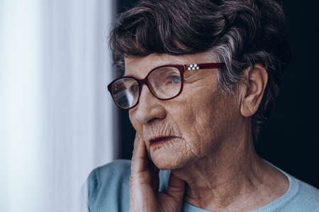 Close-up of elderly womans face with glasses, worried at home