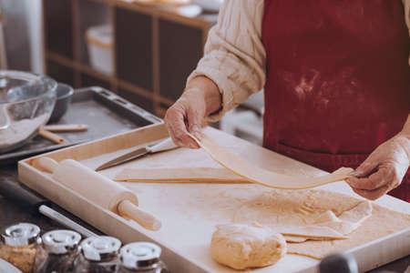 Close-up van persoon die deeg voor deegwaren op houten raad met deegrol voorbereiden
