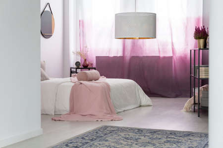 White lamp above grey carpet in bedroom with pink curtains and mirror above bed with blanket