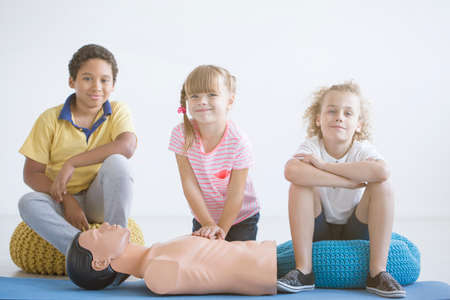 Photo of boys and a girl smiling during first aid training with medical equipment