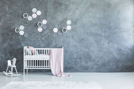 Pink blanket on white crib with pillows near white rocking horse in grey babys room interior with honeycombs on concrete wall with copy space