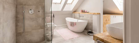 Beige rug on the floor in front of white bathtub in grey bathroom in the attic with shower set Zdjęcie Seryjne