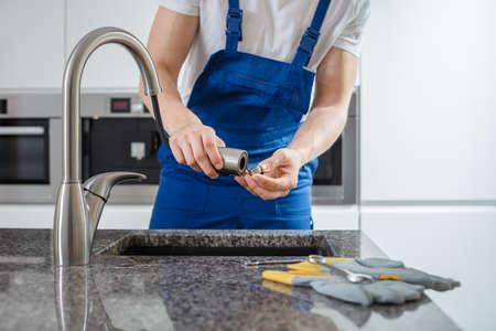 台所の蛇口を固定する青いオーバーオールの配管工のクローズアップ