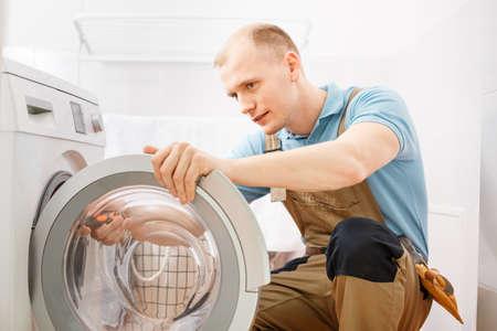 Tuttofare messo a fuoco in tuta che ripara una lavatrice nel bagno Archivio Fotografico - 91861866