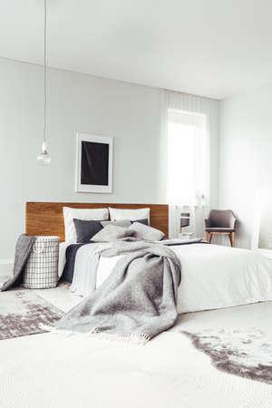 椅子と窓付きの明るいベッドルームのインテリアでキングサイズベッドの上のコピースペースを持つ白い壁に黒いポスター 写真素材