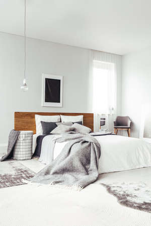 Black poster on white wall with copy space above king size bed in bright bedroom interior with chair and window