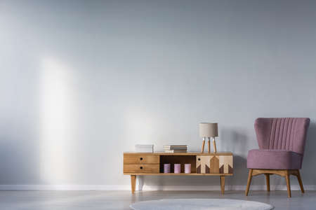 Purple armchair next to wooden cupboard with books, candles and lamp against wall with copy space in kids room interior