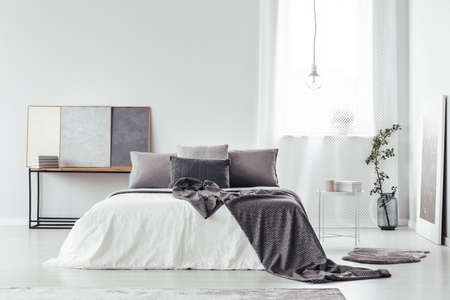 Patterned blanket on bed with grey pillows in cozy bedroom interior with vase, posters and copy space on white wall