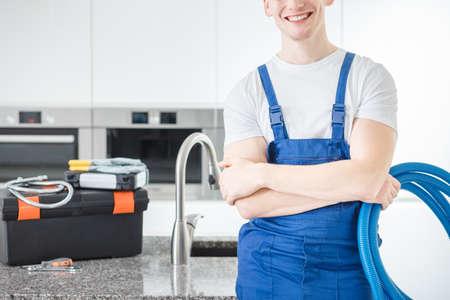 カウンタートップに機器を備えたキッチンにプラスチックパイプを備えた青いオーバーオールで笑顔のハンディマンのクローズアップ 写真素材