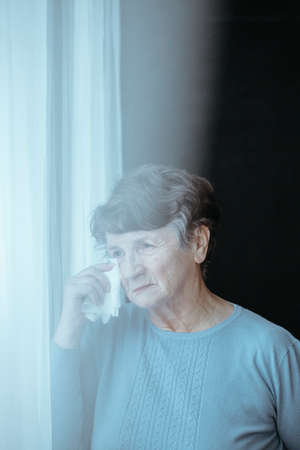 Senior woman wiping tears with tissue during mourning period