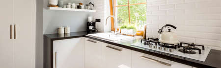 Black and white kitchen with kettle on gas stove and accessories on shelf Stock fotó