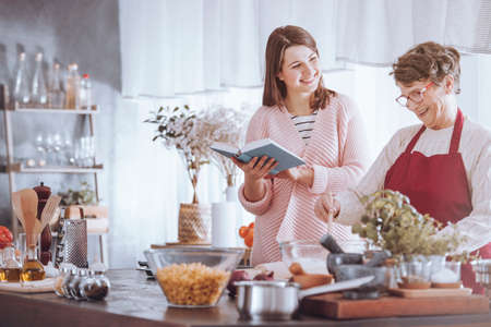 Happy grandmother mixing ingredients while cooking with granddaughter holding cookbook Stockfoto - 91862018