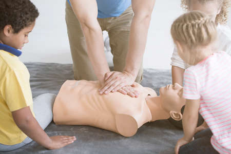Close-up photo of paramedic showing children how to perform resuscitation on medical dummy Stock Photo