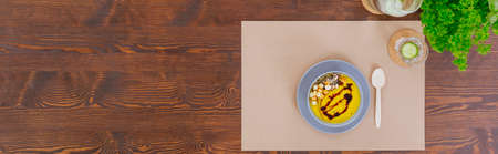 High angle of bowl with yellow vegan soup, seeds, croutons and glass of water with slice of cucumber