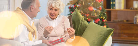 Senior woman unpacking present in christmassy decorated home