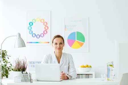 食事と栄養のノート パソコンとポスターが付いている白いオフィスのランプと机に座っての笑顔の専門家