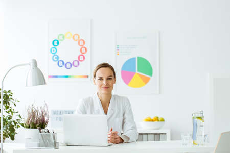 Smiling expert on diet and nutrition sitting at desk with laptop and lamp in white office with posters