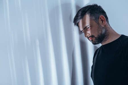 Lichtstralen die op een depressieve man schijnen met zwarte ringen om zijn ogen