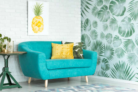 Yellow pillow on turquoise couch against brick wall with pineapple poster in sitting room with leaves wallpaper Stockfoto